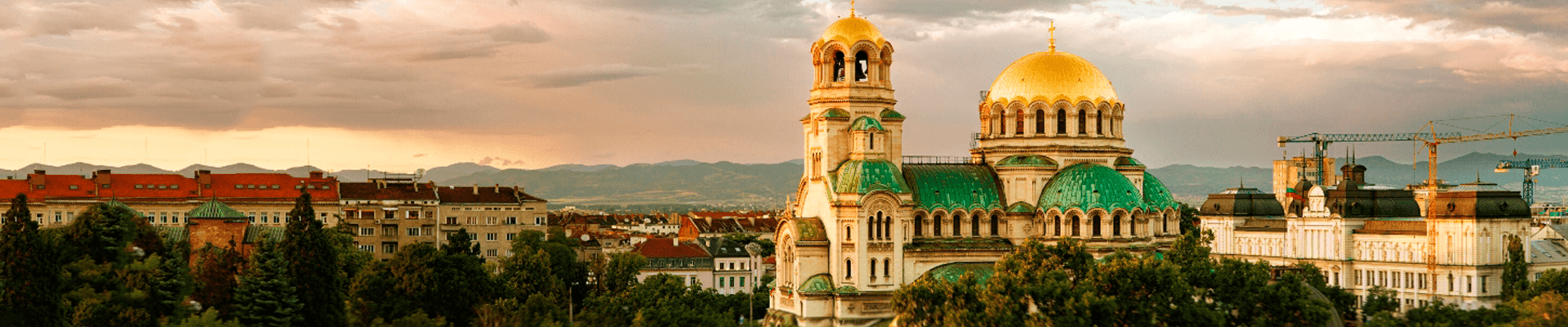 A golden domed cathedral with green tiles rises above a city in Israel
